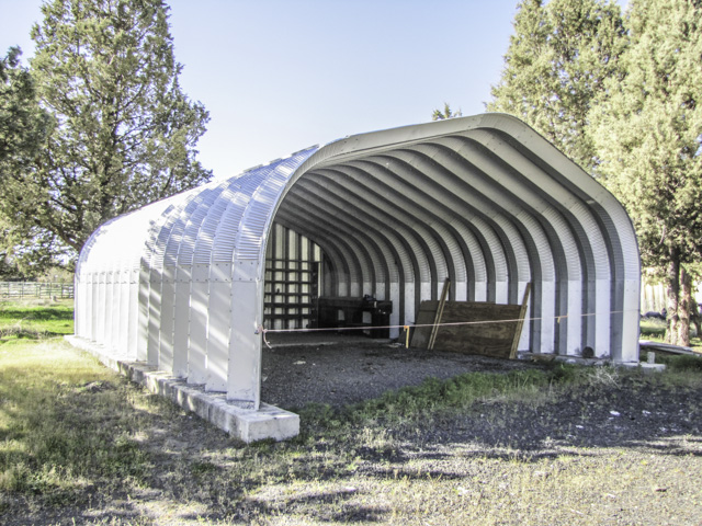 Nearly 5 acre home-site with garage/shop and  storage building.